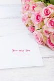 Bouquet of pink roses with blue ribbon for present on a vintage wooden background Stock Photo