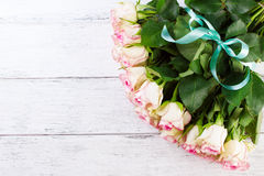 Bouquet of pink roses with blue ribbon for present on a vintage wooden background, copy space Royalty Free Stock Photos