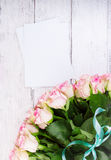Bouquet of pink roses with blue ribbon for present on a vintage wooden background, copy space Royalty Free Stock Images