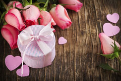 Bouquet of pink roses and gift box on wooden background Stock Photos
