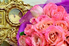 Bouquet of pink roses lying on the background of an old clock stock image
