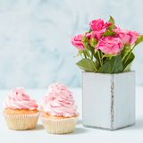 Bouquet of pink roses in retro shabby chic vase and cupcake with cream decoration. Bouquet of pink roses in retro shabby chic vase and cupcake with cream Stock Photo