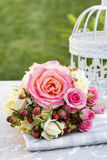 Bouquet of pink roses and vintage white bird cage Stock Image