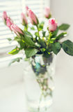 Bouquet of pink roses on the windowsill during bright sunny day Stock Photos