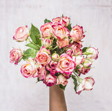 Bouquet of pink shrub roses in the hand of the girl gift on March 8 wooden rustic background top view Stock Image