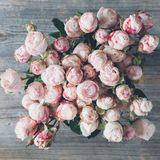 Bouquet of pink shrub roses in vase. Wedding flowers. Top view. Pink shrub roses bouquet of wedding flowers on wooden background. Closeup view. Vintage retro stock image