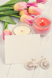Bouquet of pink tulips with blank card and lit candles Stock Images