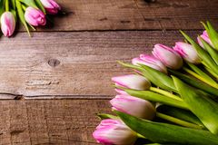 Pink tulips; on old wooden background. Bouquet of; pink tulips flowers on old wooden background; flat lay; copy space Royalty Free Stock Images