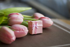 Bouquet of pink tulips with gift box on table Royalty Free Stock Image