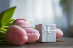Bouquet of pink tulips with gift box on table Stock Photography