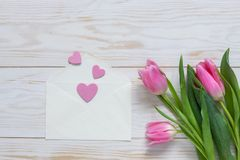Bouquet of pink tulips and hearts pattern in paper envelope. Top view, close-up, flat lay on white wooden background.  stock photography