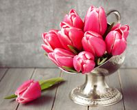 Bouquet of pink tulips in metal vase on wooden background Royalty Free Stock Image