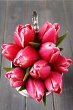 Bouquet of pink tulips in metal vase on wooden background Stock Images