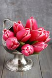 Bouquet of pink tulips in metal vase on wooden background Royalty Free Stock Images
