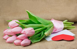 A bouquet of pink tulips with satin ribbon, envelope and heart Stock Photo