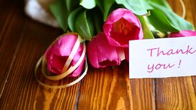 Bouquet of pink tulips. On a wooden table