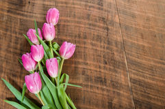 Bouquet of pink tulips on a wooden table Stock Photos