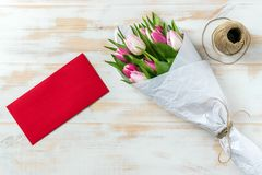 Bouquet of pink tulips wrapped in white paper. And red envelope on a wooden table. Flat lay. Love concept Stock Photography