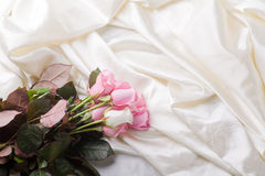 Bouquet of pink and white roses laying in silk Royalty Free Stock Image