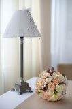 Bouquet of  pink and white roses on the table near the lamp with Royalty Free Stock Image