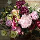 Bouquet of pink, yellow and purple peonies in a vase. On the table stock image