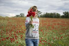 Woman in a field of poppies with a bouquet royalty free stock images