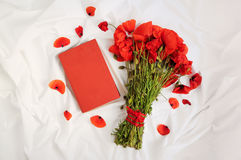 Bouquet of poppies and book. Bunch of fresh red poppies and red book on a white background Stock Photography