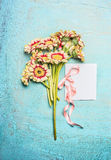 Bouquet of pretty flowers with bow and white blank card on turquoise shabby chic background royalty free stock image