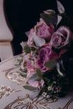 Bouquet of purple flowers lies close up. A bouquet of purple flowers lies on a chair close-up beautiful white pink lying wedding design decor decoration bridal stock image