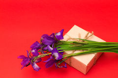 Bouquet of purple iris flowers and a box with a gift on a red  b Royalty Free Stock Image