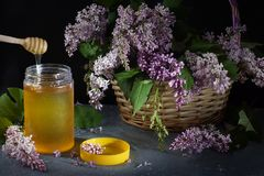 A bouquet of purple lilacs in a wicker basket on a dark background next to a jar of honey and a yellow lid on the table.  stock photos