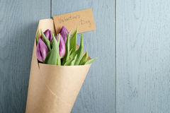 Bouquet of purple tulips in craft paper on blue wood table with paper card for valentines day Stock Photography