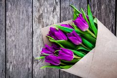 Bouquet of purple tulips on a rustic background closeup Stock Photos
