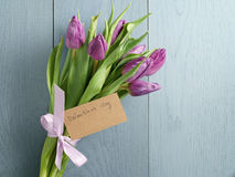 Bouquet of purple tulips tied with ribbon on blue wood table with paper card for valentines day Stock Photography
