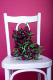 Bouquet of purple tulips on white chair Stock Photos