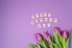 Bouquet of purple tulips and wood letters on violet background. Mother day. Flat lay, top view Royalty Free Stock Image