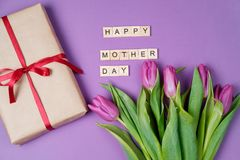 Bouquet of purple tulips and wood letters on violet background. Mother day. Flat lay, top view Stock Image