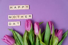 Bouquet of purple tulips and wood letters on violet background. Mother day. Flat lay, top view Stock Photos
