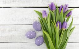 Bouquet of purpleviolet tulips and painted easter eggs on whit Stock Photo