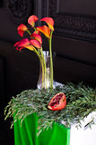 Bouquet of red calla lilies in a glass vase with a pomegranate and eucalyptus Royalty Free Stock Images
