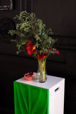 Bouquet of red calla lilies in a glass vase with a pomegranate and eucalyptus Stock Photography