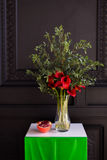 Bouquet of red calla lilies in a glass vase with a pomegranate and eucalyptus Stock Photos