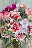 Bouquet of red carnations and purple orchid flowers Royalty Free Stock Image