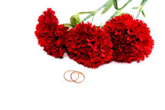 Bouquet of red carnations and wedding rings Stock Photography