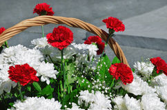 Bouquet of red carnations and white chrysanthemums in a basket Stock Photo