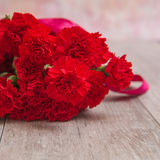 Bouquet of red carnations on wooden background Royalty Free Stock Photo