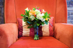 Bouquet on Red Chair. Colorful Floral Bouquet Sitting on a Plush Red Chair Stock Photo