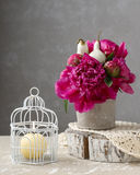 Bouquet of red peonies and scented candle in vintage birdcage Royalty Free Stock Photos