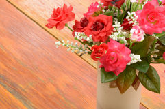 Bouquet red and pink rose in white vase on wood floor. The Royalty Free Stock Photo
