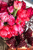 A bouquet of red and pink roses, peonies with grapes and pomegranate closeup Stock Photo